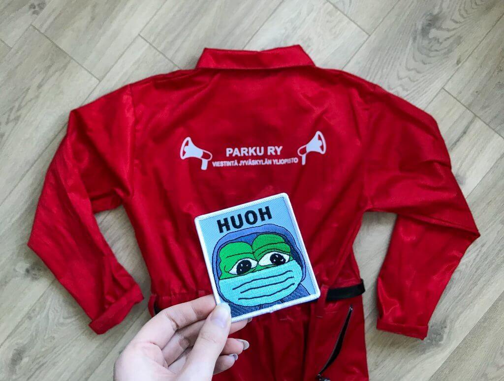"""Punaiset opiskelijahaalarit lattialla. Käsi pitelee haalarimerkkiä, jossa pettyneen oloinen sammakko sanoo """"huoh"""""""